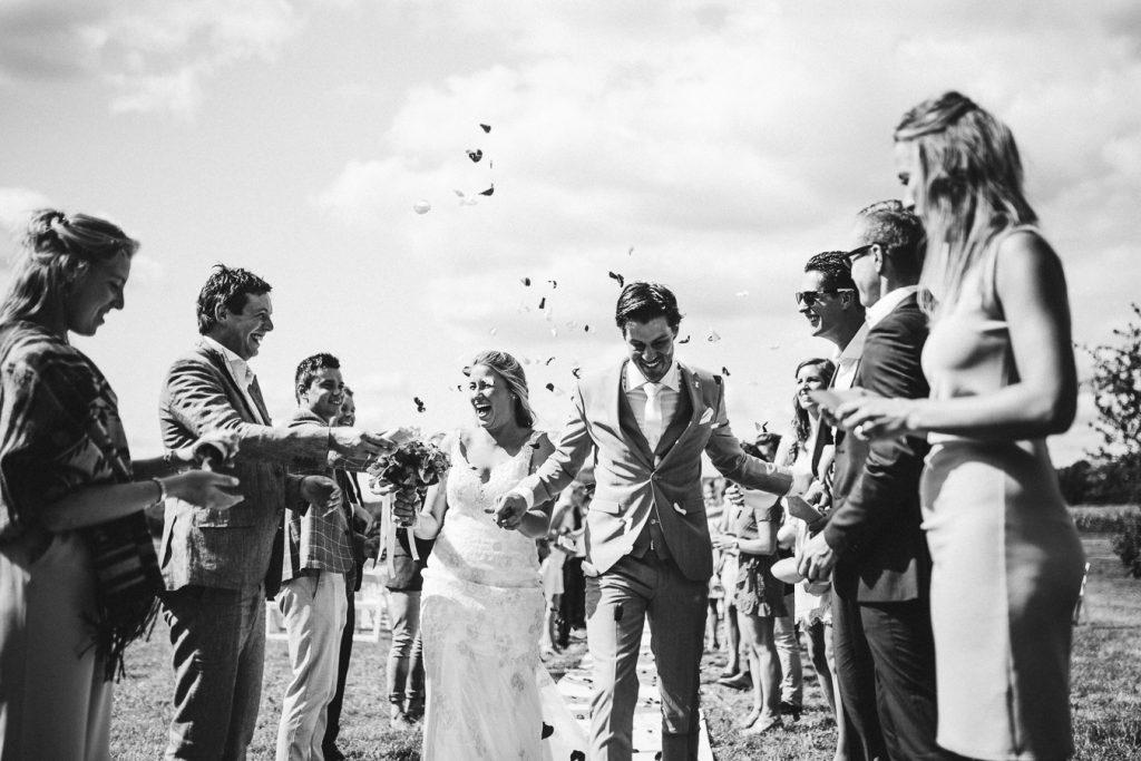 Bruid en bruidegom lopen door erehaag van gasten die rozenblaadjes in de lucht gooien tijdens bruiloft thuis op erf van oude boerderij trouwfotograaf Apeldoorn