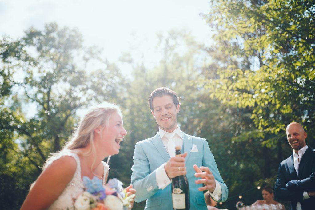 Bruidegom popt de champagnefles open en bruid lacht tijdens bruiloft thuis op erf van oude boerderij trouwfotograaf Apeldoorn