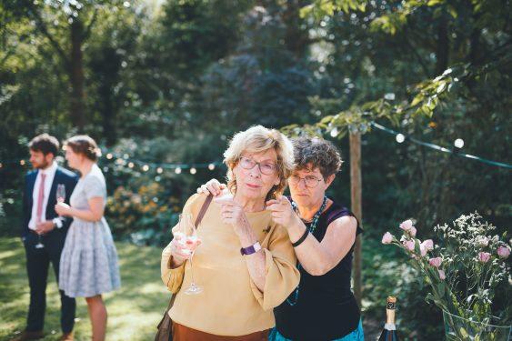 Bruiloftsgasten kijken en wijzen naar iets tijdens bruiloft thuis op erf van oude boerderij trouwfotograaf Apeldoorn