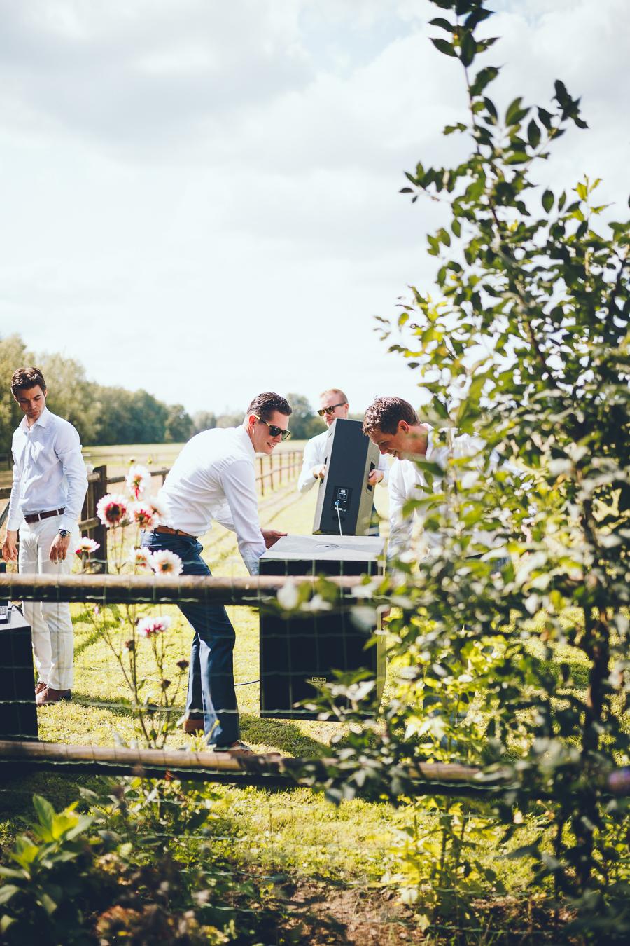 Jongemannen tillen de geluidsinstallatie van het weiland naar het borrelgedeelte .tijdens bruiloft thuis op erf van oude boerderij trouwfotograaf Apeldoorn
