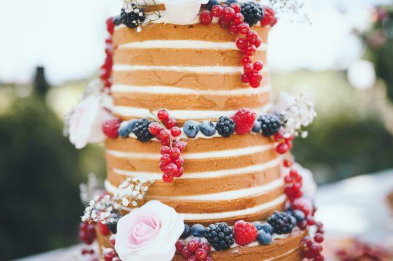 Bruidstaart met 4 lagen en verschillende laagjes fruit rozen en verse bessen staat op een tafel tijdens bruiloft thuis op erf van oude boerderij trouwfotograaf Apeldoorn