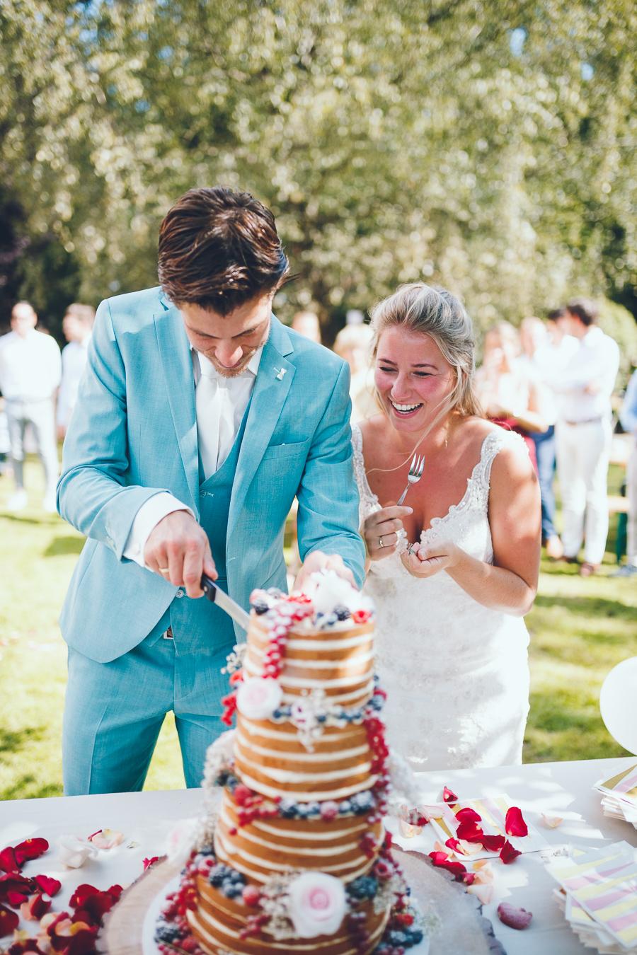 Bruidspaar snijdt bruidstaart met vier lagen en rozen en rood fruit aan en lacht tijdens bruiloft thuis op erf van oude boerderij trouwfotograaf Apeldoorn