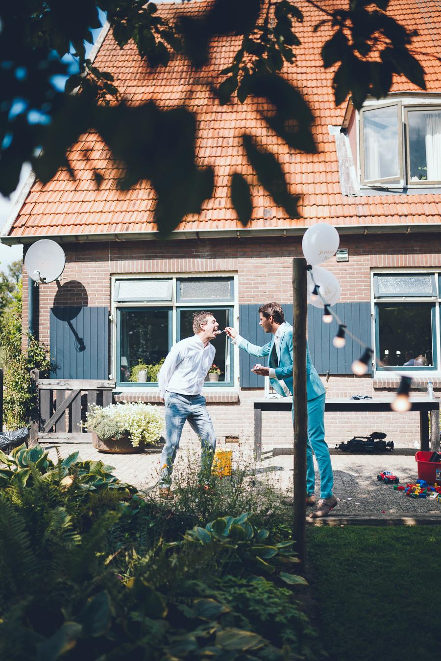 Bruidegom voert een hapje taart aan een van zijn vrienden tijdens bruiloft thuis op erf van oude boerderij trouwfotograaf Apeldoorn