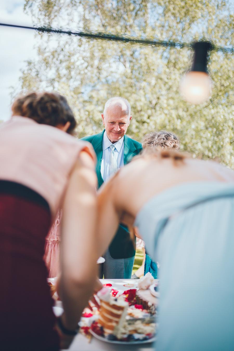 Trouwambtenaar kijkt verlekkerd naar de bruidstaart terwijl de ceremoniemeesters de taart snijden tijdens bruiloft thuis op erf van oude boerderij trouwfotograaf Apeldoorn
