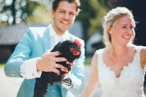 Bruidegom houdt kip vast die hij heeft gekregen van zijn vrienden tijdens bruiloft thuis op erf van oude boerderij trouwfotograaf Apeldoorn