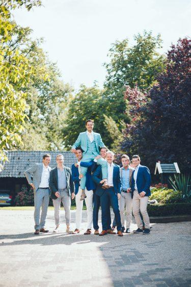 Groepsfoto met bruidegom en een groep vrienden die hem optillen tijdens bruiloft thuis op erf van oude boerderij trouwfotograaf Apeldoorn