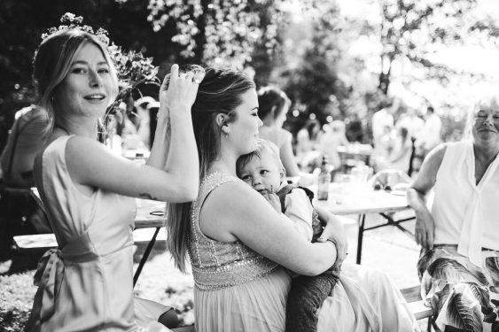 Vermoeid kindje op schoot bij moeder wiens haar wordt gedaan door haar zus tijdens bruiloft thuis op erf van oude boerderij trouwfotograaf Apeldoorn