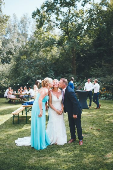 Bruid wordt gekust op haar beide wangen door haar vader en moeder en ze kijkt erg blijtijdens bruiloft thuis op erf van oude boerderij trouwfotograaf Apeldoorn