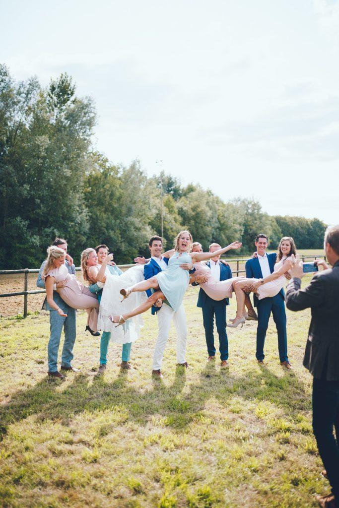 Groepsfoto met stelletjes waar de mannen hun vriendinnen in de lucht tillen tijdens bruiloft thuis op erf van oude boerderij trouwfotograaf Apeldoorn