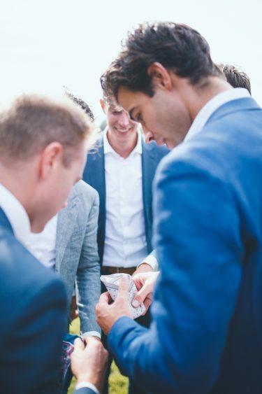 Foto van groep mannen die een zakdoek vouwen tijdens bruiloft thuis op erf van oude boerderij trouwfotograaf Apeldoorn