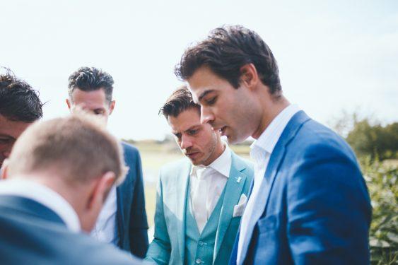Foto van groep mannen die geconcentreerd kijken naar iemand die een zakdoek vouwt tijdens bruiloft thuis op erf van oude boerderij trouwfotograaf Apeldoorn
