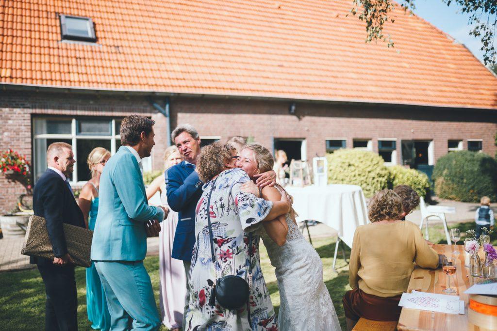 Bruid wordt geknuffeld en gefeliciteerd door vrouwelijke gast tijdens bruiloft thuis op erf van oude boerderij trouwfotograaf Apeldoorn