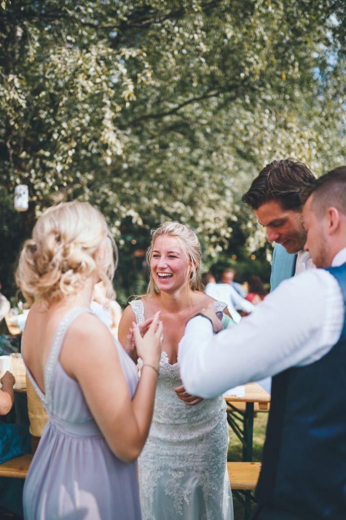 Bruid en bruidegom krijgen cadeau en de bruid lacht tijdens bruiloft thuis op erf van oude boerderij trouwfotograaf Apeldoorn