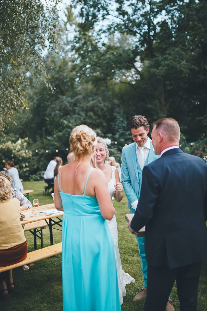 Bruid en bruidegom krijgen cadeau van ouders van de bruid tijdens bruiloft thuis op erf van oude boerderij trouwfotograaf Apeldoorn