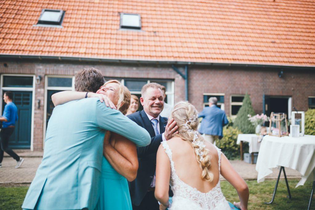 Ouders van de bruid feliciteren het bruidspaar tijdens bruiloft thuis op erf van oude boerderij trouwfotograaf Apeldoorn