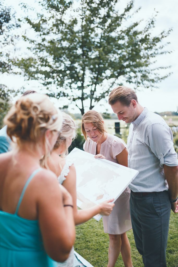 Bevriend stel overhandigt scratchmap cadeau aan bruidspaar tijdens bruiloft thuis op erf van oude boerderij trouwfotograaf Apeldoorn