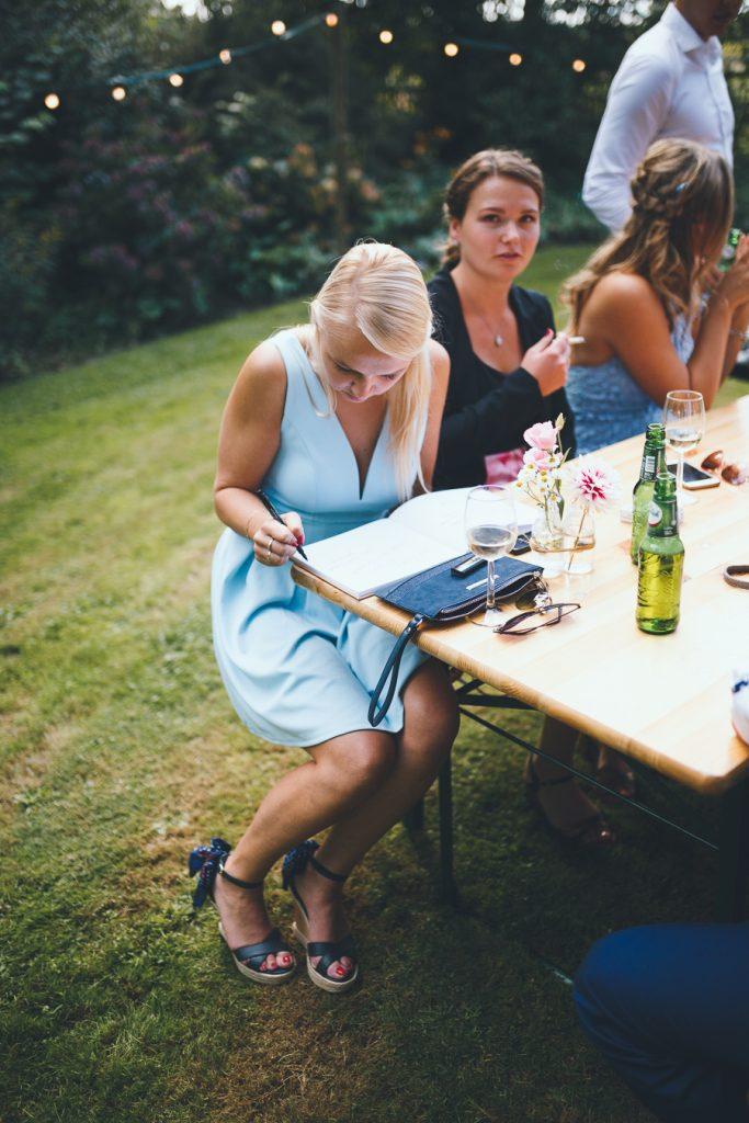 Vriendin zit op bankje van biertafel en schrijft in gastenboek tijdens bruiloft thuis op erf van oude boerderij trouwfotograaf Apeldoorn
