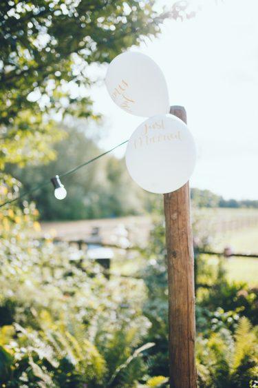 Witte ballonnen met in het goud just married erop geschreven tijdens bruiloft thuis op erf van oude boerderij trouwfotograaf Apeldoorn