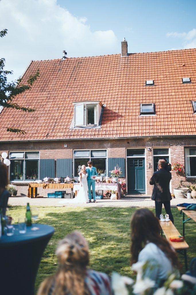Bruidspaar spreekt gasten toe voor start van het diner tijdens bruiloft thuis op erf van oude boerderij trouwfotograaf Apeldoorn
