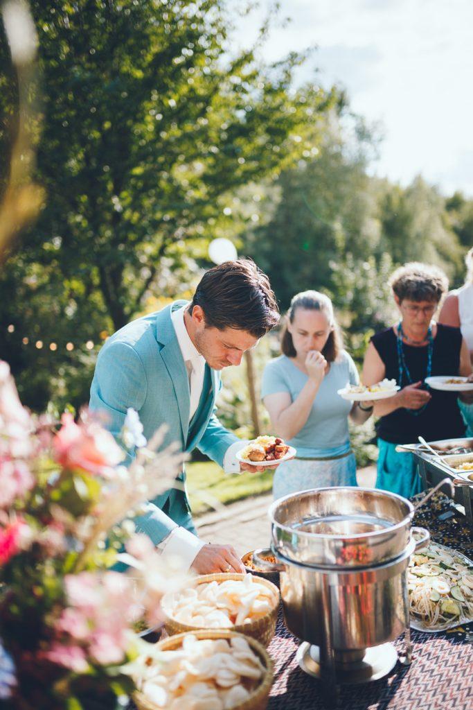 Bruidegom schept eten van Indonesisch buffet op tijdens bruiloft thuis op erf van oude boerderij trouwfotograaf Apeldoorn