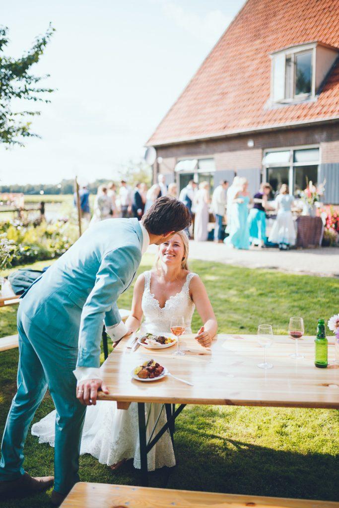 Bruid en bruidegom zitten alvast aan tafel met een bord met Indonesisch eten en kijken elkaar aan tijdens bruiloft thuis op erf van oude boerderij trouwfotograaf Apeldoorn