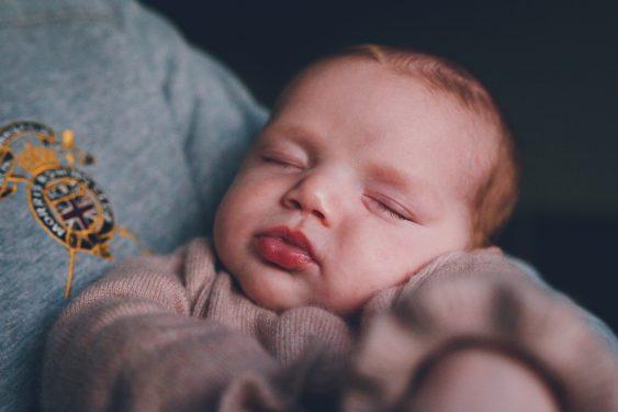 Baby in armen van vader tijdens lifestyle newbornfotograaf Apeldoorn