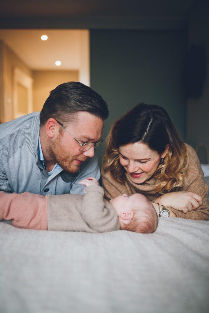 Ouders lachen naar baby op bed in slaapkamer tijdens lifestyle newbornfotograaf Apeldoorn