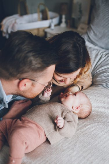 Baby lacht naar ouders op bed tijdens lifestyle newbornfotograaf Apeldoorn