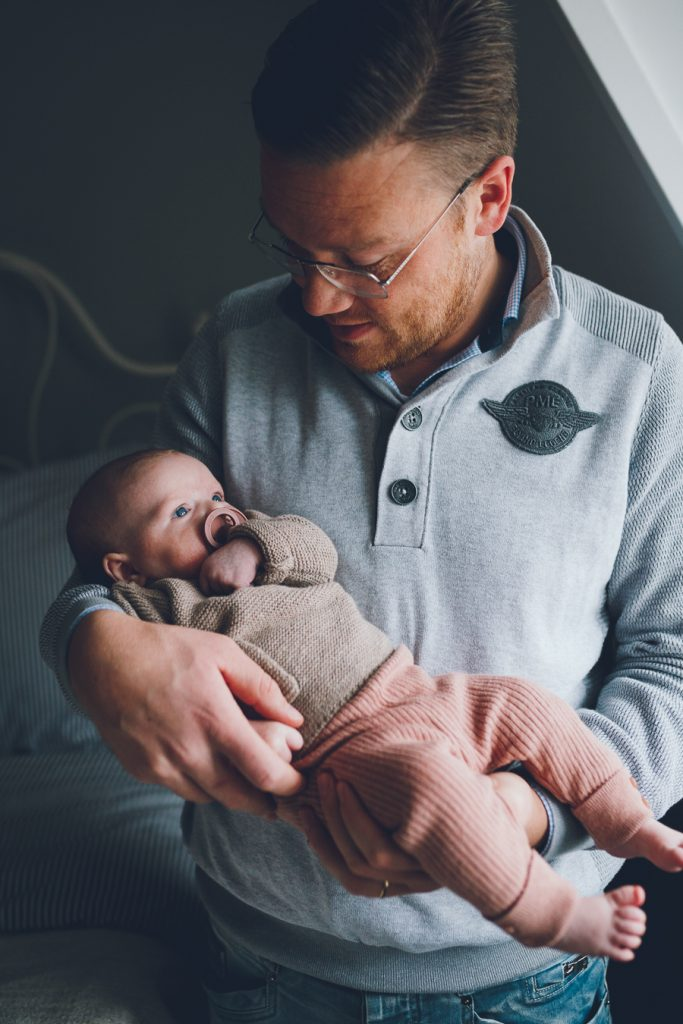 Vader houdt dochter baby vast tijdens lifestyle newbornfotograaf Apeldoorn