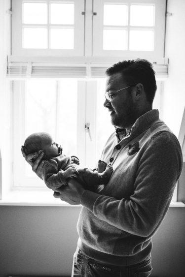 Vader houdt dochter in z'n armen zwart wit tijdens lifestyle newbornfotograaf Apeldoorn