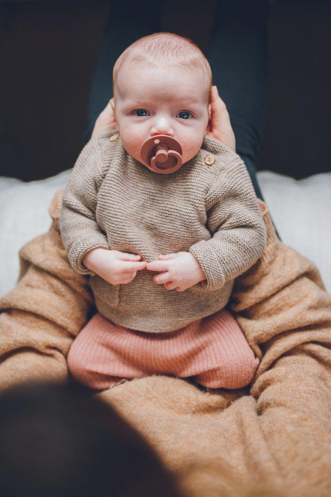 Baby kijkt je aan met roze speen in mond tijdens lifestyle newbornfotograaf Apeldoorn