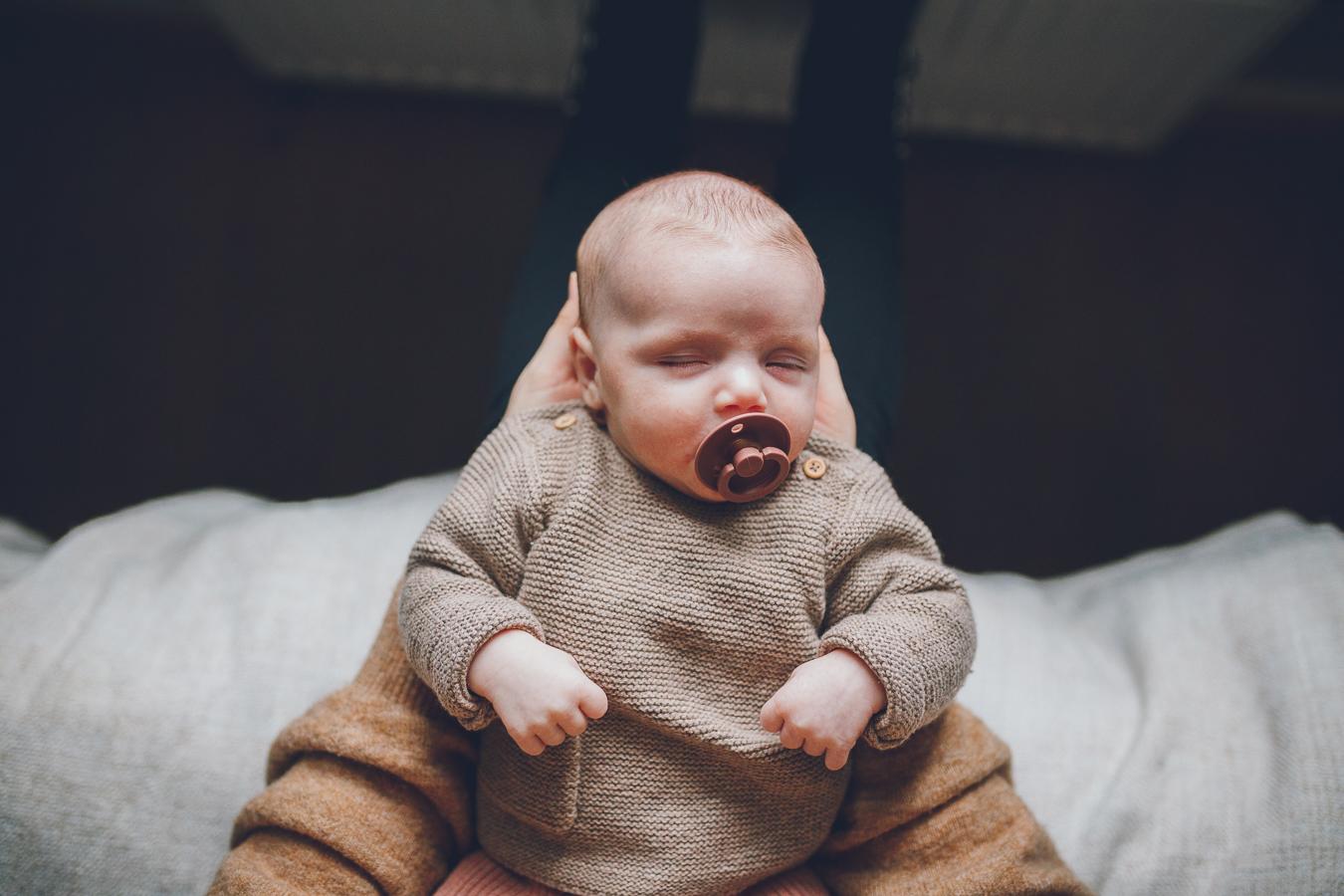 Baby met roze speen in mond slaapt in handen van moeder tijdens lifestyle newbornfotograaf Apeldoorn