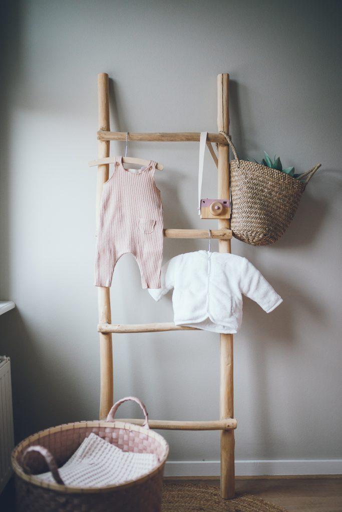 Babykleertjes aan ladder in babykamer tijdens lifestyle newbornfotograaf Apeldoorn