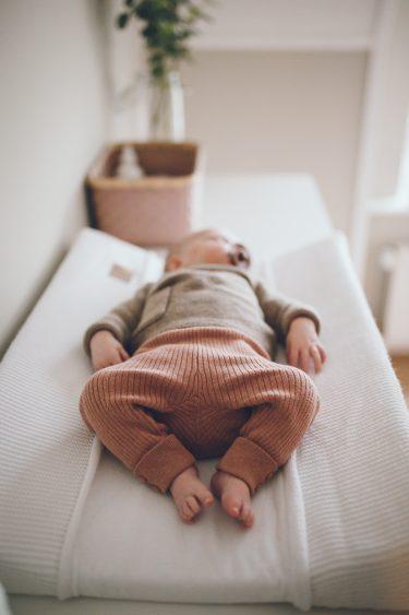 Slapende baby op aankleedkussen in babykamer tijdens lifestyle newbornfotograaf Apeldoorn