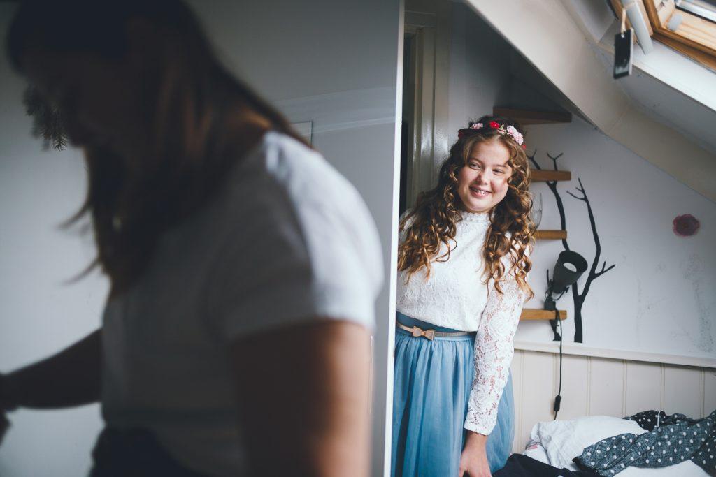 Zusje kijkt om hoek deur waar bruid zich klaarmaakt op bruiloft trouwfotograaf in Nunspeet