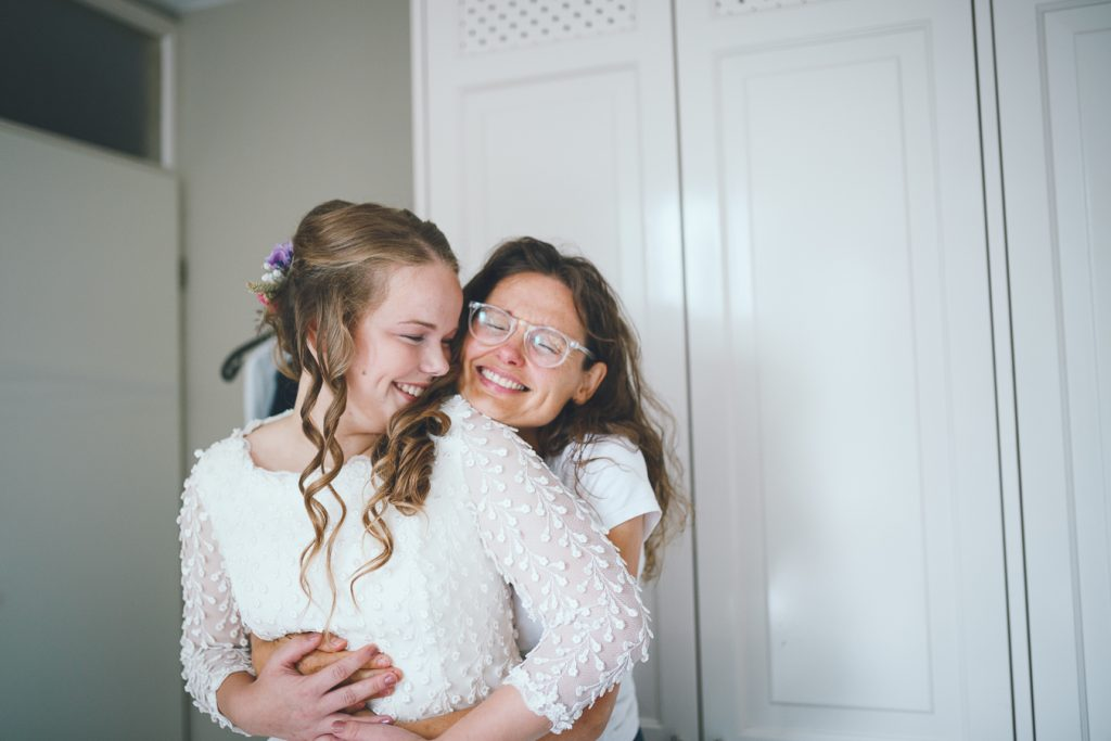 Moeder van de bruid omhelst bruid bij aantrekken jurk op bruiloft trouwfotograaf in Nunspeet