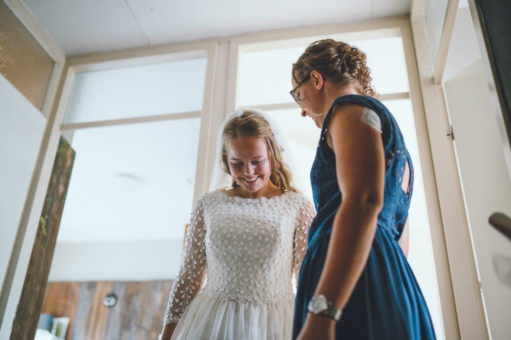 Bruid en beste vriendin bovenaan de trap vlak voor first look op bruiloft trouwfotograaf in Nunspeet