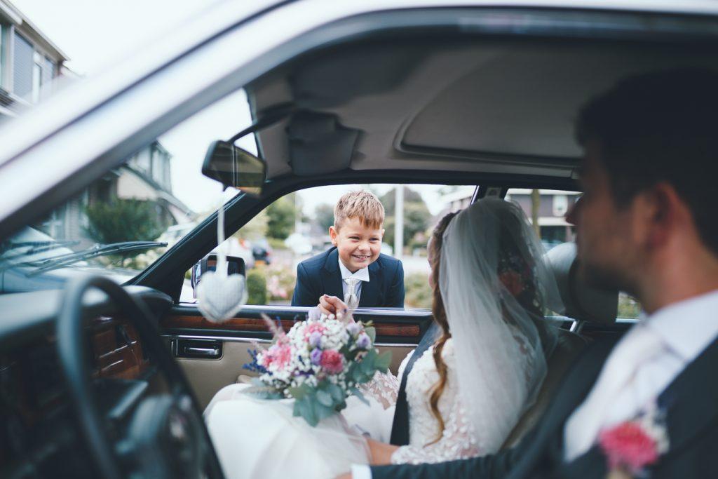 Broertje van de bruid kijkt door raam trouwauto naar bruidspaar op bruiloft trouwfotograaf in Nunspeet