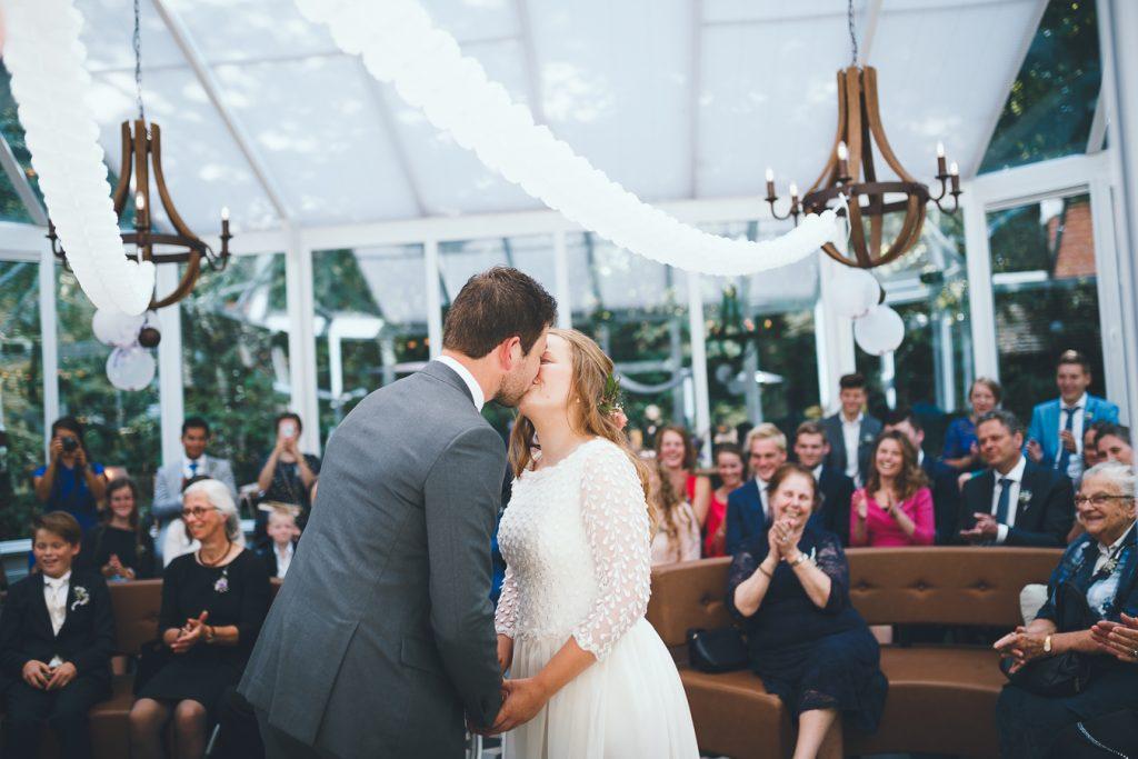 De kus tijdens trouwceremonie op bruiloft trouwfotograaf in Nunspeet