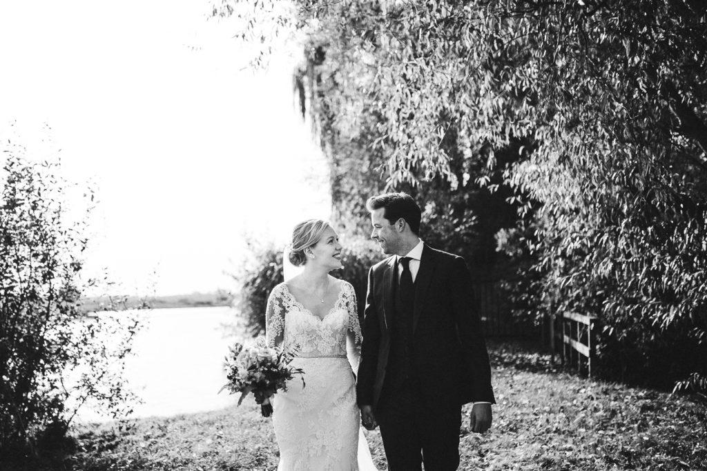 Bruidspaar staat hand in hand naast elkaar en kijkt elkaar aan op bruiloft trouwfotograaf in Den Bosch