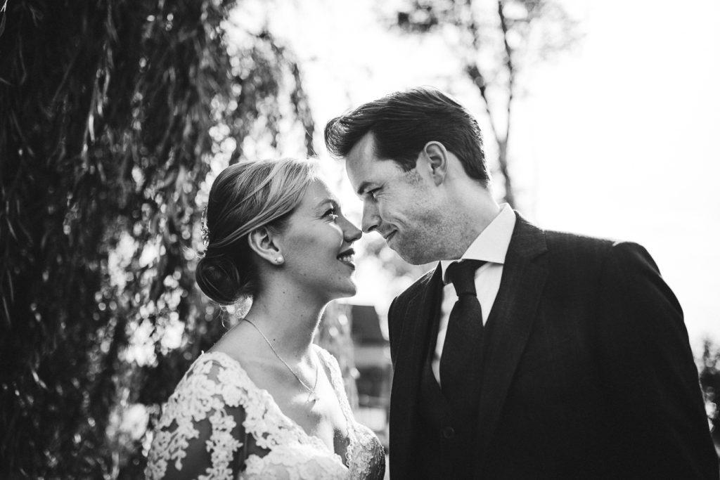 Bruiddspaar staat tegenover elkaar en kijkt elkaar close up aan op bruiloft trouwfotograaf in Den Bosch