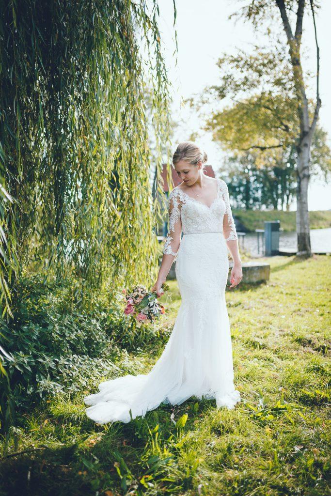 Bruid bij oude wilg met boeket kijkt naar beneden op bruiloft trouwfotograaf in Den Bosch