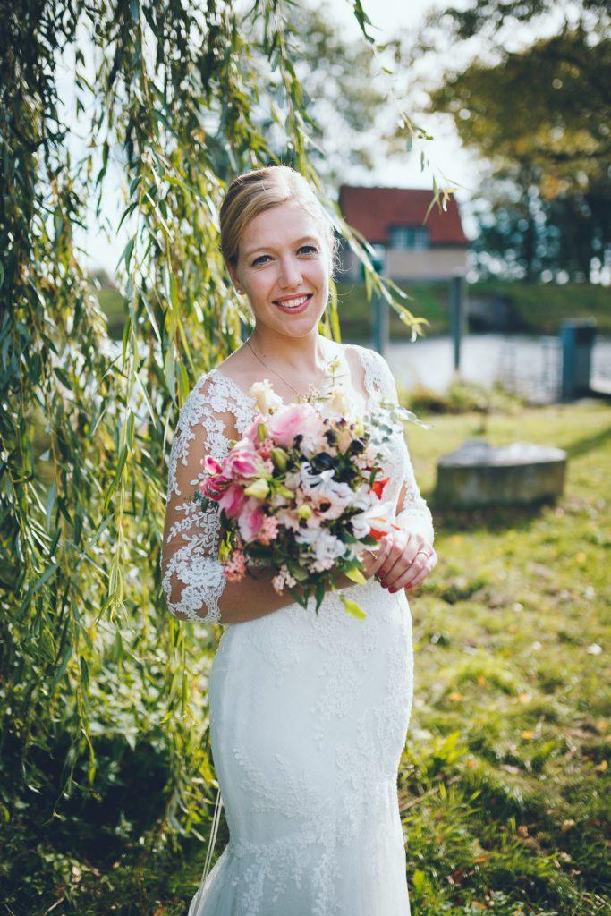 Bruid met boeket onder oude wilg op bruiloft trouwfotograaf in Den Bosch