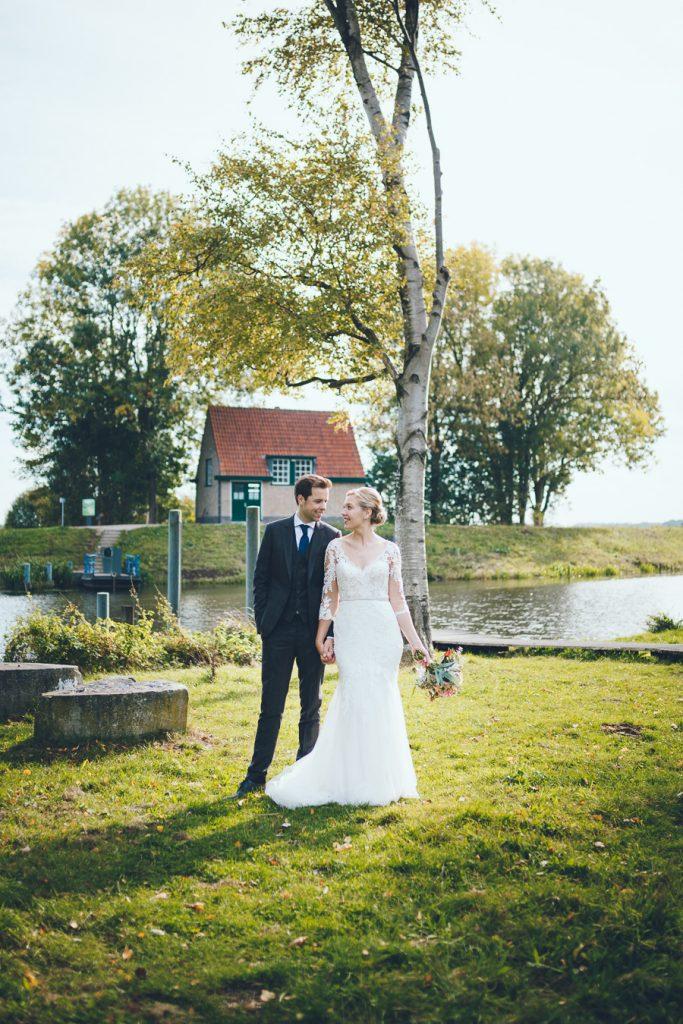 Bruid en bruidegom staan naast elkaar en kijken elkaar aan op bruiloft trouwfotograaf in Den Bosch