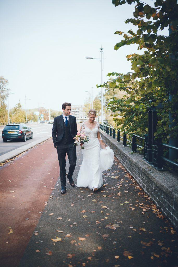 Bruid en bruidegom lopen over brug op bruiloft trouwfotograaf in Den Bosch