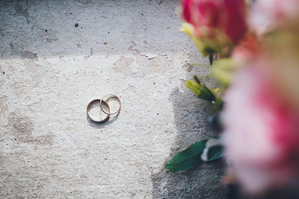 Trouwringen stilleven close up op betonnen ondervloer met boeket op bruiloft trouwfotograaf in Den Bosch