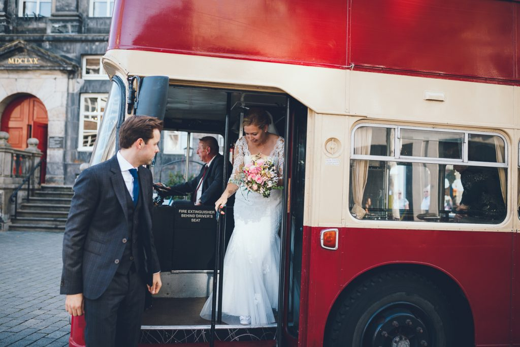 Bruidspaar stapt uit oude Engelse bus voor stadhuis op bruiloft trouwfotograaf in Den Bosch