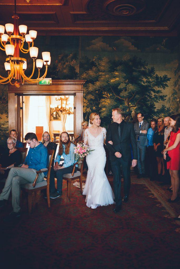 Bruid wordt begeleid door vader naar altaar in oude stadhuis van Den Bosch op bruiloft trouwfotograaf in Den Bosch