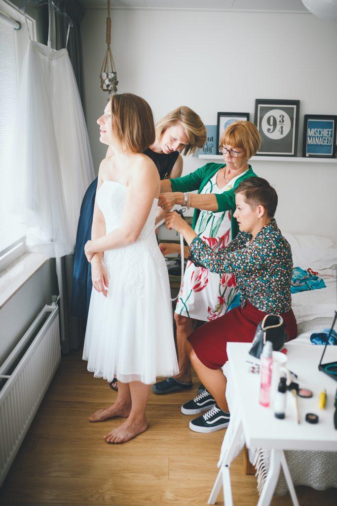 Voorbereidingen bruid aantrekken jurk hulp van drie vrouwen tijdens bruiloft in fruittuin trouwfotograaf Amsterdam Apeldoorn