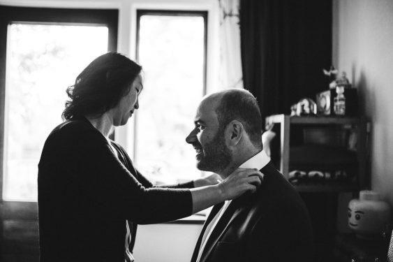 Bruidegom wordt in pak geholpen zwart wit tijdens bruiloft in fruittuin trouwfotograaf Amsterdam Apeldoorn